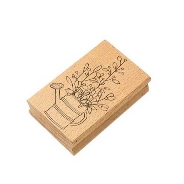 sello de madera regadera con plantas
